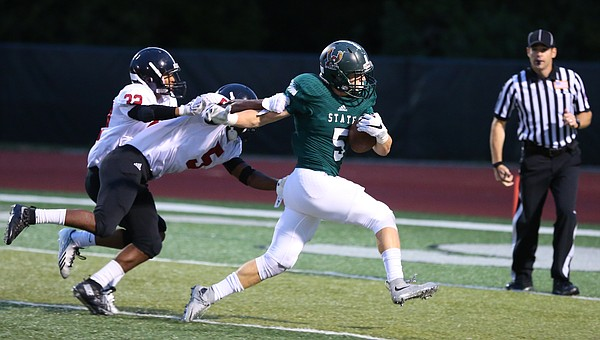 Free State running back Sam Skwarlo (5) shrugs off Lawrence High defenders Ivan Hollins (5) and defensive back Dante Jackson (32) on his way in for a touchdown during the first half on Friday, Sept. 17, 2015 at Free State High School.