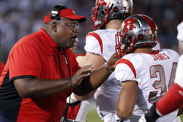Rutgers interim head coach Norries Wilson, center, talks with Rutgers running back Paul James (34) on the sidelines during the first half of an NCAA college football game against Penn State in State College, Pa., Saturday, Sept. 19, 2015. (AP Photo/Gene J. Puskar)