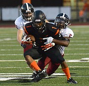 Shawnee Mission Northwest's Robert Strain (1) gets wrapped up by Lawrence High's Cade Burghart (left) and Ivan Hollins in the Lions' 41-6 victory Thursday, Sept. 24, 2015, in Overland Park.