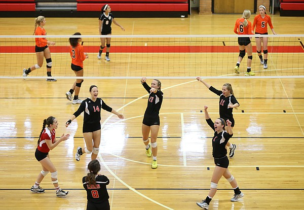 Lawrence High players celebrate a point against Shawnee Mission Northwest during a volleyball tri on Thursday, Sept. 24, 2015 at Lawrence High School.