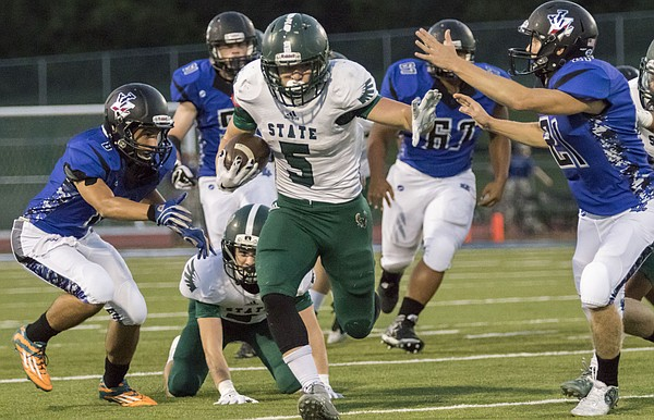 Free State senior running back Sam Skwarlo (5) breaks through the Leavenworth defense on his way to a 60 yard first quarter touchdown during their football game Friday night in Leavenworth.