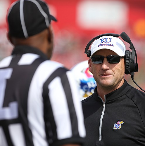Kansas head coach David Beaty confers with a game official after what some on the Kansas bench thought was a missed face mask call against Rutgers during the third quarter on Saturday, Sept. 26, 2015 at High Point Solutions Stadium in Piscataway, New Jersey.