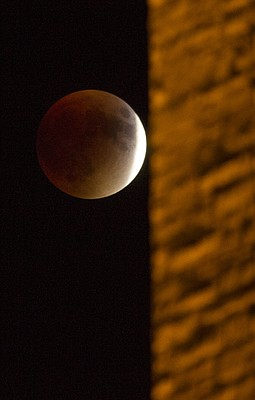 A blood moon moves behind the illuminated stones of the Campanile on the Kansas University campus Sunday night, Sept. 27, 2015.