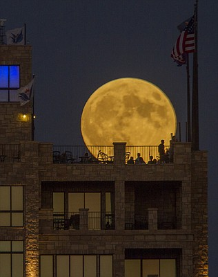 People gather at The Nest on Ninth at The Oread to watch a harvest moon, a full moon nearest the September equinox, come up Sunday night, Sept. 27, 2015. Later there was an eclipse of the moon which has led many to call this event a rare super blood moon. This combination of events won't happen again until 2033.
