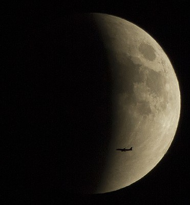 A plane is framed against the eclipsing moon Sunday night, Sept. 27, 2015. A harvest moon and the blood moon eclipse has led many to call this event a rare super blood moon. This combination of events won't happen again until 2033.