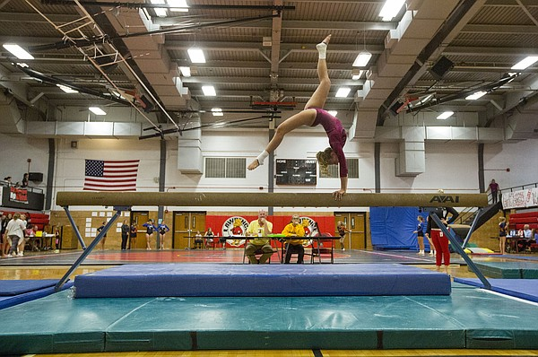 Lawrence High's Ashley Ammann performs on the balance beam  Wednesday evening at LHS. The Lions hosted Olathe East, Olathe Northwest and Free State in a gymnastics quad.