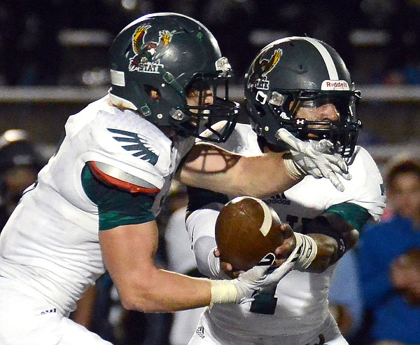 Bryce Torneden hands the ball off to Sam Skwarlo as Free State played Shawnee Mission East Friday in Overland Park. The Firebirds won, 32-20.