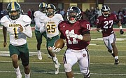 On the first play from scrimmage, Lawrence High senior running back JD Woods breaks through the Shawnee Mission South defense for a 70 yard touchdown run during their game Friday night at LHS. The Lions won, 42-6, and improved their record to 5-0 on the season.