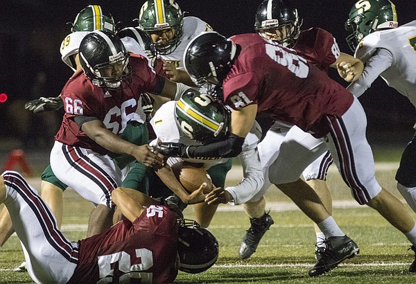 Lawrence High's Jams Murry (66), Santino Gee (25) and Price Morgan (81) work to bring down Shawnee Mission South junior Cam Union (1)  during their game Friday night at LHS. The Lions won, 42-6, and improved their record to 5-0 on the season.