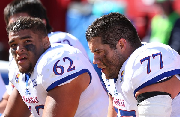 Kansas offensive linemen Joe Gibson (77) and D'Andre Banks (62) catch a breather on the bench during the second quarter on Saturday, Oct. 3, 2015 at Jack Trice Stadium in Ames, Iowa.