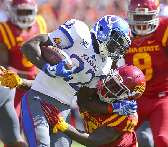 Kansas running back Ke'aun Kinner (22) is dragged down by Iowa State defensive back Brian Peavy (10) during the second quarter on Saturday, Oct. 3, 2015 at Jack Trice Stadium in Ames, Iowa.