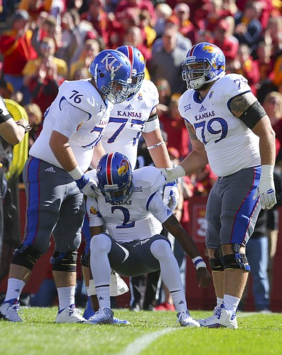 Kansas quarterback Montell Cozart (2) is helped off the turf by Kansas offensive linemen Bryan Peters (76), Joe Gibson (77), Jordan Shelley-Smith (79) after a sack during the second quarter on Saturday, Oct. 3, 2015 at Jack Trice Stadium in Ames, Iowa.