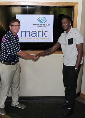 Colby Wilson, executive director of the Boys & Girls Club of Lawrence, and Mario Chalmers. The club received a $5,000 donation from the Mario V. Chalmers Foundation toward a new teen center.