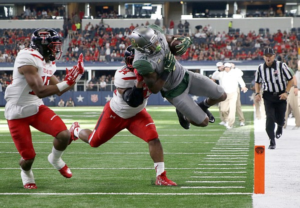 Baylor wide receiver Corey Coleman leaps into the end zone for a score in front of Texas Tech defensive back Keenon Ward (15) and linebacker D'Vonta Hinton (34) in the second half of an NCAA college football game Saturday, Oct. 3, 2015, in Arlington, Texas. Baylor won 63-35. (AP Photo/Roger Steinman)