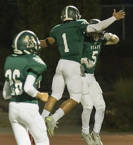 Free State seniors Bryce Torneden (1) and Sam Skwarlo (5) celebrate a touchdown run by Skwarlo during their game against Shawnee Mission South Friday evening at FSHS.