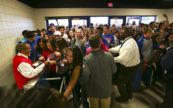Kansas University students jam through the turnstiles as security workers try to settle the crowd shortly after opening the doors for Late Night in the Phog, Friday, Oct. 9, 2015 at Allen Fieldhouse.