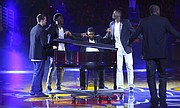 Kansas players Clay Young, left, LaGerald Vick, Cheick Diallo and Dwight Coleby huddle around freshman forward Carlton Bragg as he entertains the fieldhouse with his talents on the piano during Late Night in the Phog, Friday, Oct. 9, 2015 at Allen Fieldhouse.