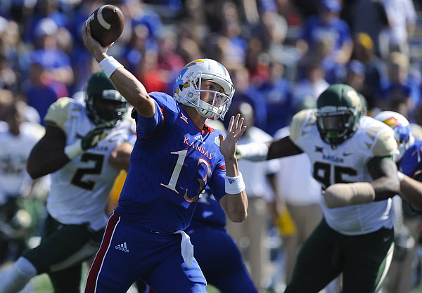 Kansas quarterback Ryan Willis (13) throws to a receiver as the Baylor defense closes in during the second quarter on Saturday, Oct. 10, 2015 at Memorial Stadium.