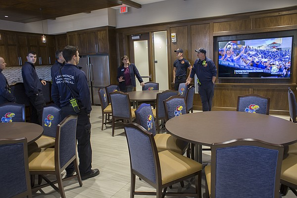 Diana Robertson, director of KU student housing, right, introduces Lawrence-Douglas County Fire and Medical personnel to a multipurpose room and kitchen inside the new $11.2 million McCarthy Hall, which houses the Kansas men's basketball team.