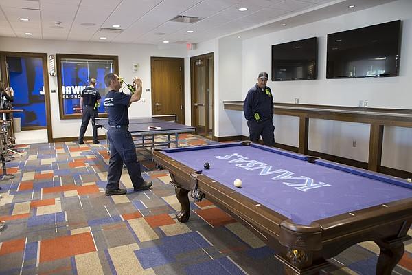 Lawrence-Douglas County Fire and Medical personnel tour a recreation room at the new $11.2 million McCarthy Hall, which houses the Kansas men's basketball team.