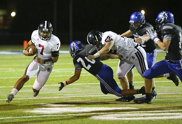 Lawrence High quarterback Alan Clothier catches a block as lineman Jake Unruh (52) pushes aside Olathe Northwest defensive back Charles Elvin (20) during the third quarter on Thursday, Oct. 15, 2015 in Olathe.