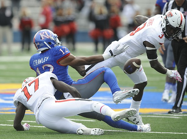 Kansas wide receiver Darious Crawley (12) has the ball knocked away after a catch by Texas Tech defensive backs Thierry Nguema (17) and J.J. Gaines (3) during the quarter on Saturday, Oct. 17, 2015 at Memorial Stadium.