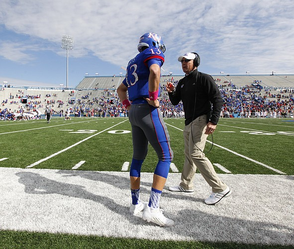 Kansas head coach David Beaty talks with a discouraged  Ryan Willis (13) after Willis' interception which was returned for a Texas Tech touchdown late in the fourth quarter on Saturday, Oct. 17, 2015 at Memorial Stadium.