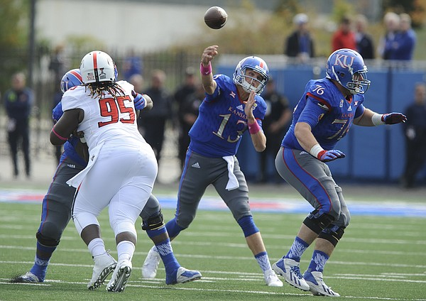 Kansas quarterback Ryan Willis (13) throws between blockers during the third quarter on Saturday, Oct. 17, 2015 at Memorial Stadium.