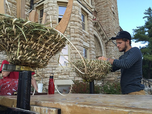 "Kansas University art major Jake Kaufmann, a senior from Elkhorn, Neb., weaves a ""sun hive"" Tuesday afternoon, Oct. 20, 2015, in front of Dyche Hall. Kaufmann was part of associate professor of art Matt Burke's Social and Sustainable Art Practices class. Burke said the hives will ultimately be used by local farms as a more sustainable and nature-emulative way to house bee colonies than the more typical boxes."