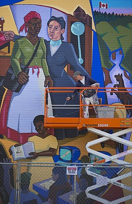 "Lawrence muralist Dave Loewenstein tosses a paint brush in a bucket as he repaints his mural, ""A Thousand Miles Away,"" on the north side of Cordley Elementary School, Tuesday, Oct. 20, 2015. The mural depicts an Underground Railroad scene involving a slave named Lizzie and Lawrence abolitionists Rev. Richard Cordley (not pictured) and his wife Mary."