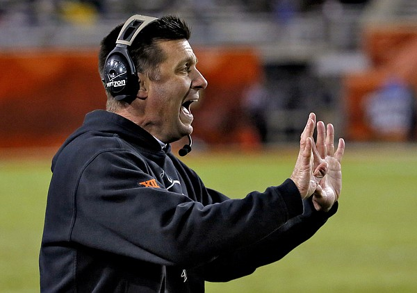 Oklahoma State coach Mike Gundy signals during the second half of the Cactus Bowl NCAA college football game against Washington, Friday, Jan. 2, 2015, in Tempe, Ariz. (AP Photo/Matt York)