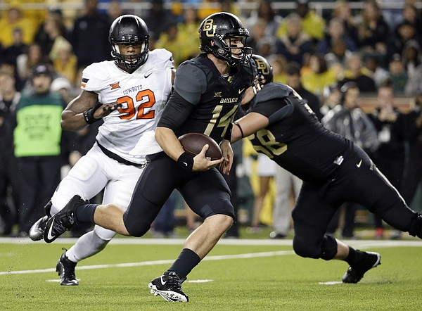 Baylor quarterback Bryce Petty (14) keeps the ball and runs under pressure from Oklahoma State's Jimmy Bean (92) in the first half of an NCAA college football game, Saturday, Nov. 22, 2014, in Waco, Texas. (AP Photo/Tony Gutierrez)