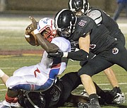Lawrence High senior Price Morgan (81) lays a hit on Olathe North senior running back Vinson Shabazz, left, as Price and teammate Tanner Green bring down Shabazz for a loss during their game Friday evening at LHS.