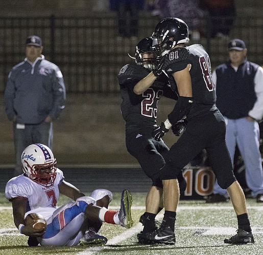 Lawrence High's Erik Shackelford (23) and Price Morgan (81) celebrate after bring down Olathe North senior running back Vinson Shabazz (3) for a loss during their game Friday evening at LHS.
