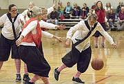 Mary Pat Pellett, right, of Lawrence, chases down a loose ball during the first game of the Granny Basketball League in Kansas Saturday evening at Holcom Park Recreational Center, 2700 W. 27th Street.