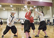 Michele Clark, of Lawrence, center, catches a pass under the basket as Mary Pat Pellett, left, of Lawrence, and Diane Knowles, left, of Topeka, defend during the first game of the Granny Basketball League in Kansas Saturday evening at Holcom Park Recreational Center, 2700 W 27th Street.
