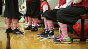 Nikes are paired with traditional 1920s women's basketball uniforms including colorful striped stockings during the first game of the Granny Basketball League in Kansas Saturday evening at Holcom Park Recreational Center, 2700 W 27th Street.