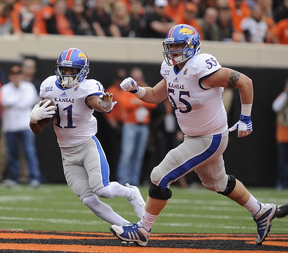 Kansas wide receiver Tre' Parmalee (11) and Kansas offensive lineman Jacob Bragg (55) turn up the field afte a catch in the second quarter on Saturday, Oct. 24, 2015 at T. Boone Pickens Stadium in Stillwater, Okla.