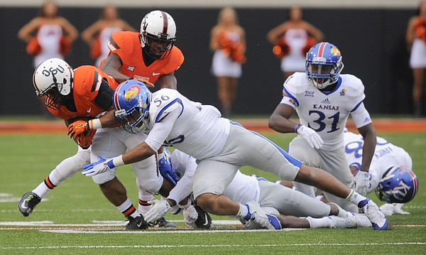 Kansas defensive end Anthony Olobia (56) delivers a hit to Oklahoma State running back Raymond Taylor (30) during the fourth quarter on Saturday, Oct. 24, 2015 at T. Boone Pickens Stadium in Stillwater, Okla.