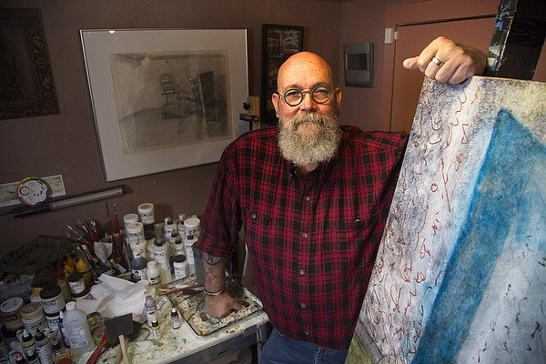Marty Olson stands in his studio at 416 E. Ninth. Many of the paintings and prints he creates there are displayed in his hair salon, Do's Deluxe, which he's owned for nearly 40 years and resides in the same building as Olson's art studio.