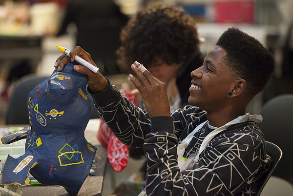 """Van Go apprentice artist Derrius Wilson, 16, has a laugh with others at his table as he works on his """"Van-imal"""" on Tuesday, Oct. 27, 2015, at Van Go Inc., 715 New Jersey Street."""