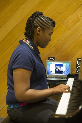 Teneill Childers, 12, a seventh-grader at Eisenhower Middle School in Kansas City, Kan., receives a piano lesson Thursday, Oct. 29, 2015, from Isabel Keleti, a third-year music student at Kansas University, via Skype and special pianos that reproduce the performer's movements on each instrument. Teneill is part of KU School of Music's Piano Without Borders program that remotely provides kids in need with private lessons.
