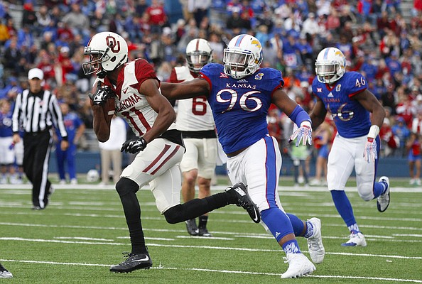 Oklahoma wide receiver Dede Westbrook (11) is snagged by Kansas defensive tackle Daniel Wise (96) during the second quarter, Saturday, Oct. 31, 2015 at Memorial Stadium.