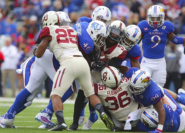 Members of the Kansas defense including Kansas defensive end Dorance Armstrong Jr. (46) bring down Oklahoma wide receiver Durron Neal (5) during the second quarter Saturday, Oct. 31, 2015 at Memorial Stadium.