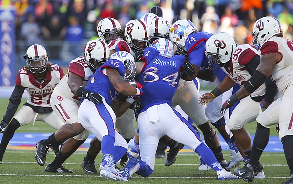 Kansas running back Taylor Cox (36) and his blocker tight end Ben Johnson (84) are stopped by a wall of Oklahoma defenders on a run during the third quarter, Saturday, Oct. 31, 2015 at Memorial Stadium.