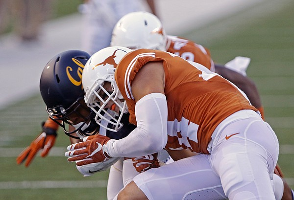 "Texas defensive back Dylan Haines, front, tackles California's Stephen Anderson during the first half of an NCAA college football game, Saturday, Sept. 19, 2015, in Austin, Texas. Haines was called for ""targeting"" and ejected from the game. (AP Photo/Michael Thomas)"