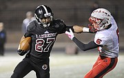 Lawrence High senior J'Mony Bryant (27) stiff-arms Shawnee Mission North's Dalton Morris during the Class 6A football playoffs on Friday night at LHS.