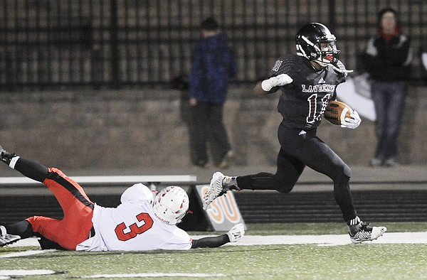 Lawrence High's  J.D. Woods (11) shakes off Shawnee Mission North's Sam Schwartz on Friday night at LHS.