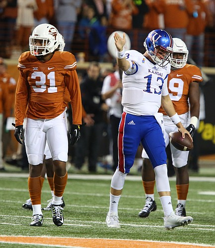 Kansas quarterback Ryan Willis (13) signals a first down next to Texas safety Jason Hall (31) during the first quarter on Saturday, Nov. 7, 2015 at Darrell K. Royal Stadium in Austin, Texas.