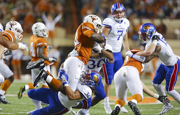 Kansas special teams player Taylor Cox wraps up Texas kick returner Kris Boyd (2) during the first quarter on Saturday, Nov. 7, 2015 at Darrell K. Royal Stadium in Austin, Texas.